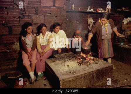 Frau kocht über eine grobe indoor Feuer, wie junge Mädchen in der Nähe von Casa de Gobierno Merida Stand in den - Stockfoto
