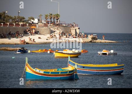 Bunt bemalte Boote mit Leuten am Strand in St. Thomas Bay in der Nähe von Marsaskala auf mediterranen Insel von - Stockfoto