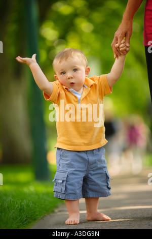 Kleinkind zu Fuß auf dem Bürgersteig - Stockfoto