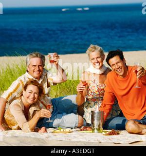 Porträt von zwei ältere Ehepaare am Strand sitzen und halten Sektgläser - Stockfoto