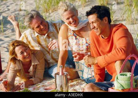 Zwei ältere Ehepaare am Strand sitzen und halten Sektgläser - Stockfoto