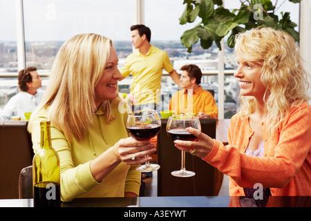 Reife Frau mit einer Mitte erwachsenen Frau einen Drink Toasten - Stockfoto
