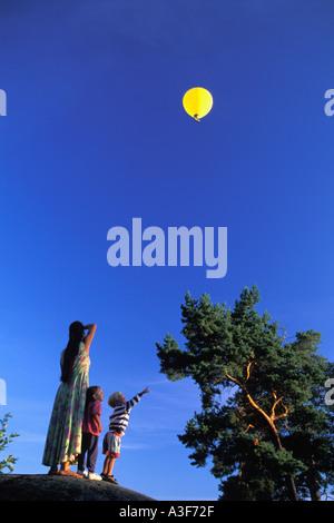 Mutter mit Kindern auf Hügel, die Ballons fliegen overhead bei Sonnenuntergang beobachten - Stockfoto