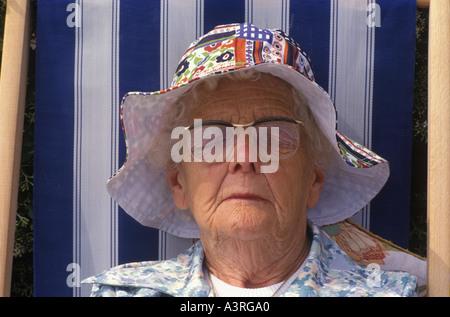 Schlafen Schlafen ältere Frau schläft ein Sonnenbad im Liegestuhl das Tragen eines Sun Motorhaube während des Urlaubs - Stockfoto