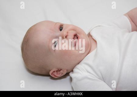Baby Wickeltisch lächelnd an übergeordnete Handauflegen - Stockfoto