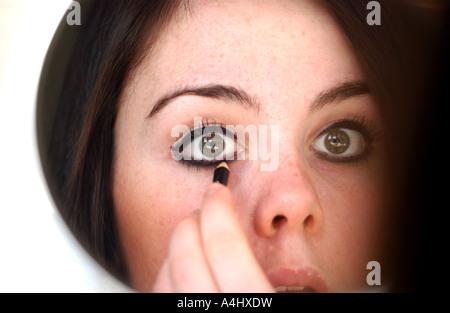 Brunette Modell junges Mädchen Teenager Anwendung Augen Make-up im Spiegel - Stockfoto