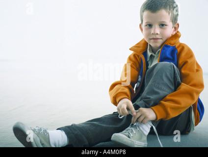 Junge sitzt auf Boden, Schuh zu binden - Stockfoto