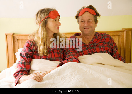 Paar im Bett mit Augenmasken auf Kopf sitzt - Stockfoto