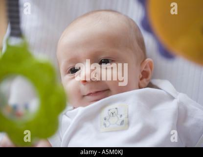 Baby lächelt bei mobile - Stockfoto