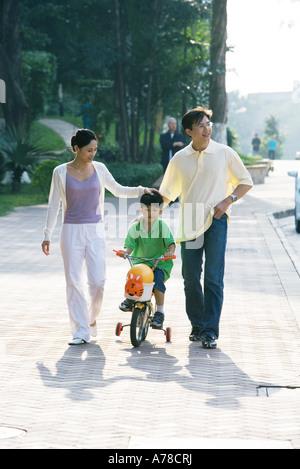 Junge Reiten Fahrrad mit Stützrädern, Eltern auf beiden Seiten, Vorderansicht - Stockfoto