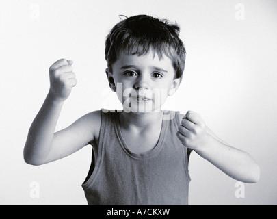 kleiner Junge Blick aggressiv mit Fäusten angehoben - Stockfoto