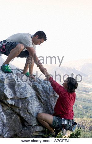 Ein Bergsteiger hilft einem anderen - Stockfoto
