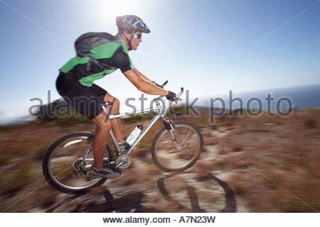 Männliche Mountainbiker Radfahren im extremen Gelände in hellem Sonnenlicht Meer im Hintergrund-Seitenansicht - Stockfoto