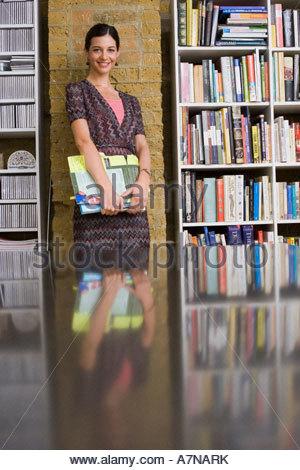 Junge Frau lehnt sich an die Wand neben Bücherregalen im Amt halten Zeitschriften, Lächeln, Porträt - Stockfoto