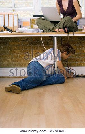 Mann Büro Bodensteckdose unterhalb der Rezeption Frau sitzt auf Schreibtisch mit Laptop Kabel einstecken - Stockfoto
