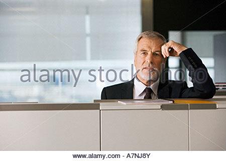 Reife Geschäftsmann stützte sich auf Aktenschrank im Büro-portrait - Stockfoto