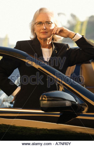 Senior Geschäftsfrau gelehnt stationären Auto lächelnd Vorderansicht Porträt - Stockfoto