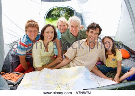 Generationsübergreifende Mehrfamilienhaus sitzen im Zelt auf camping-Ausflug Blick auf Karte, Lächeln, Porträt - Stockfoto