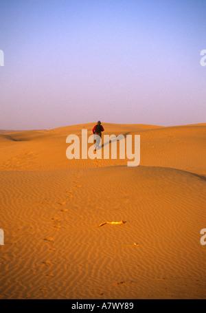 Ein Mann geht in der Wüste außerhalb Indiens Khuri in Rajasthan. - Stockfoto