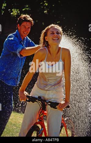 Junges Paar im Freien im Garten.  Mann Spritzen Wasser auf Frau Reiten Fahrrad. - Stockfoto