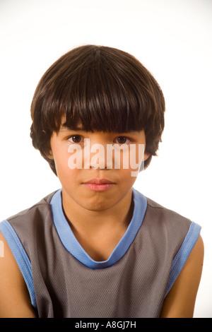 Ein 8 Jahre alter chinesischer amerikanischer Junge trägt eine kontemplative Haltung zu Hause in Kalifornien - Stockfoto