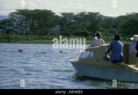 Touristen auf einem Motorboot beobachten Nilpferde am Lake Naivasha Kenia in Ostafrika - Stockfoto
