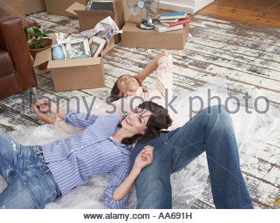 Mann und Frau liegend auf Luftpolsterfolie in Haus mit Kartons - Stockfoto