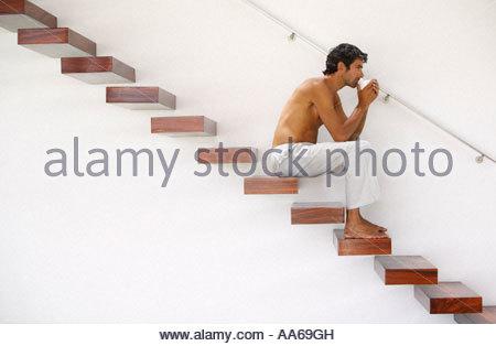 Nackter Oberkörper Mann sitzt auf der Treppe mit Becher - Stockfoto