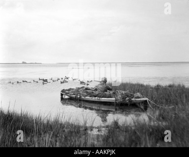 1920ER JAHRE MANN DUCK HUNTER WARTEN IN GETARNTEN SNEAKBOX ENTE BOOT BARNEGAT BAY NEW JERSEY USA - Stockfoto