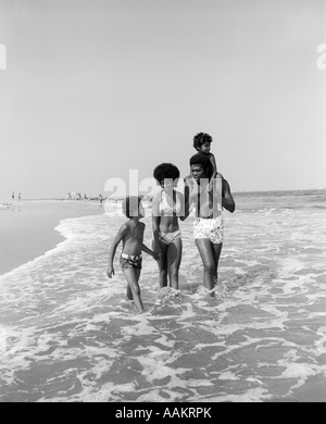 1970ER JAHREN SURFEN AFRICAN AMERICAN FAMILIE MANN VATER FRAU MUTTER ZWEI JUNGEN SÖHNE WATEN IN STRAND ENTLANG SPAZIEREN, - Stockfoto
