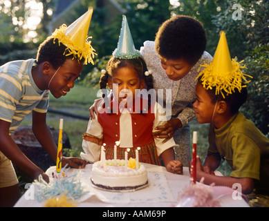 1970ER JAHREN AFRICAN AMERICAN MUTTER 3 KINDER MÄDCHEN AUSBLASEN DER KERZEN BIRTHDAY CAKE 2 BOYS IN GELBEM PAPIER - Stockfoto