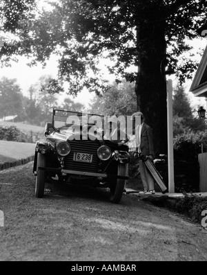 1920ER JAHREN PAAR MANN FRAU GEBEN SIE TRAGEN TASCHEN MODE REISE FREIZEIT URLAUB GOLF BAGS GEHOBENEN CABRIO AUTO - Stockfoto