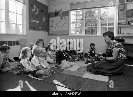 1980ER JAHREN GRUNDSCHULLEHRERIN SITZEN AUF BODEN MIT STUDENTEN SPIELEN GITARRE & SINGEN - Stockfoto