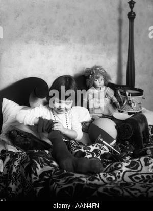 1930S 1920S MÄDCHEN IM BETT MIT STRUMPF VOLLER SPIELZEUG PUPPEN STOFFTIERE TROMMEL - Stockfoto
