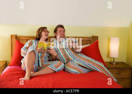 Paar passende Pyjamas im Bett tragen - Stockfoto