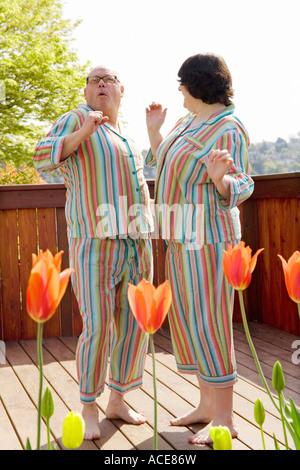 Paare tanzen auf Terrasse in passenden Pyjamas - Stockfoto