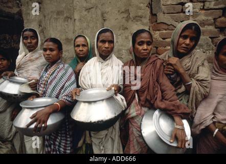 Arme Menschen mit Töpfen Schlangestehen für Lebensmittel für ihre Familie bei Mutter Teresa s Mission Kalkutta Indien - Stockfoto