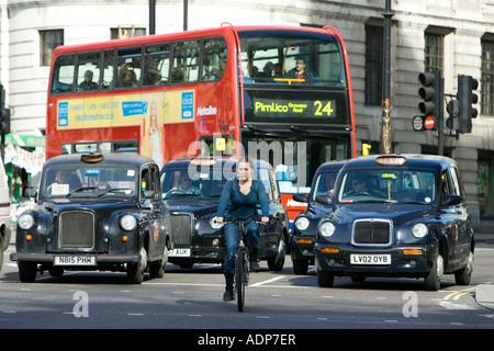 Biker vor starkem Verkehr in Trafalgar Square London Stadtzentrum England United Kingdom - Stockfoto