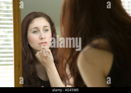 Eine Frau in einem Spiegel Anwendung machen - Stockfoto