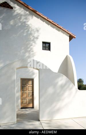 Die Haustür ein Santa Barbara Stil Zuhause gesehen durch einen Torbogen. - Stockfoto