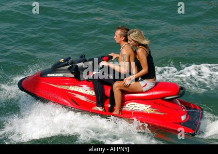 ein junger Mann und junge Frau auf einem Jetski Wassermotorräder nicht tragen Schwimmwesten im Sommer auf dem Wasser - Stockfoto