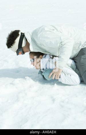 Bruder und Schwester spielen im Schnee, übereinander - Stockfoto