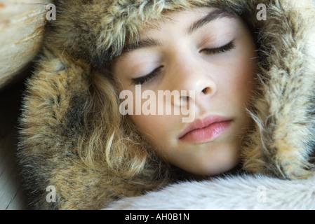 Preteen Mädchen, trägt Pelzhut, eingehüllt in Pelz Decke, schlafen, close-up portrait - Stockfoto