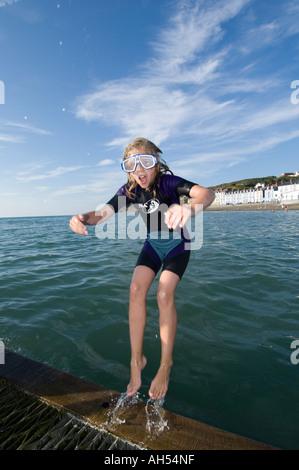 Sommer am Nachmittag - nass eine Teenager-Mädchen trägt Anzug und Schutzbrillen springen rückwärts ins Meer Aberystwyth - Stockfoto
