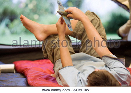 Jungen 8-10 liegend Schlafsack im Zelt auf der Wiese im Garten spielen mit Spielzeug aero Flugzeug Rückansicht - Stockfoto