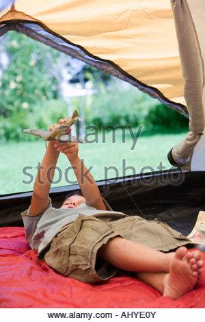 Jungen 8-10 am Schlafsack im Zelt auf der Wiese im Garten spielen mit Spielzeug aero Flugzeug Neigung liegen - Stockfoto