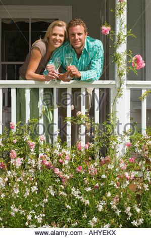 Paar steht auf der Veranda mit Blick auf Sommer Garten Holding Champagner Flöten lächelnd Vorderansicht Porträt - Stockfoto