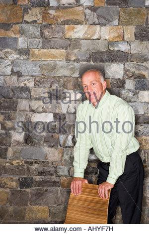 Reifer Mann stehend neben Steinmauer gelehnt auf Stuhl, Lächeln, Porträt - Stockfoto