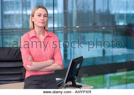 Blonde Unternehmerin in rosa Bluse, lehnt sich an den Schreibtisch im Büro, verschränkten Armen, Porträt, Fenster - Stockfoto
