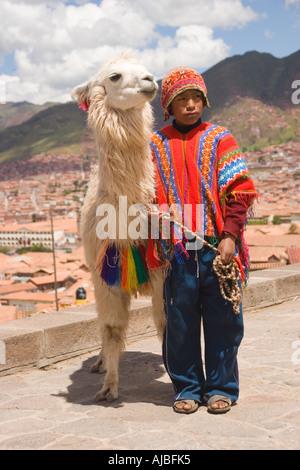 Junge gekleidet traditionell peruanische Junge mit Alpaka vor Stadtansicht von Cusco Peru - Stockfoto